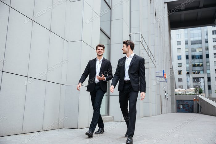 Two businessmen walking and talking in the city