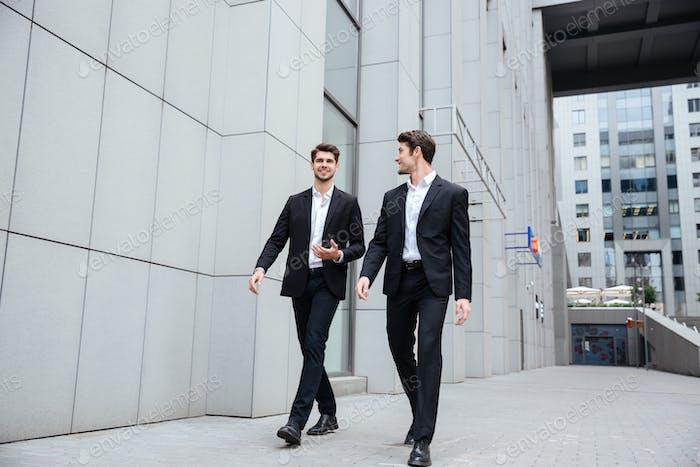 Два бизнесмена ходят и разговаривают в городе