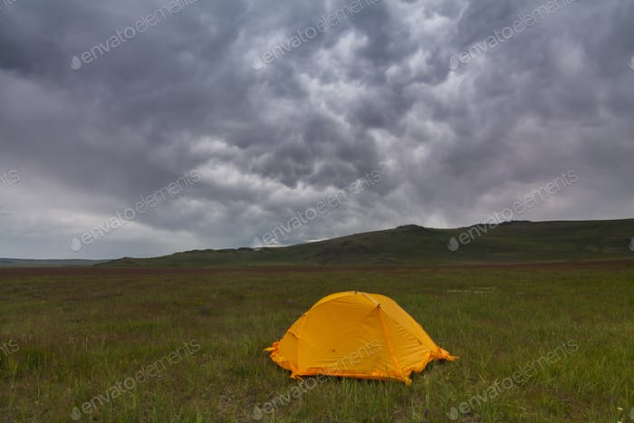 Orange tent on the background of rain clouds