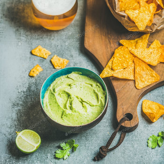 Mexican corn chips, fresh guacamole sauce and beer, square crop