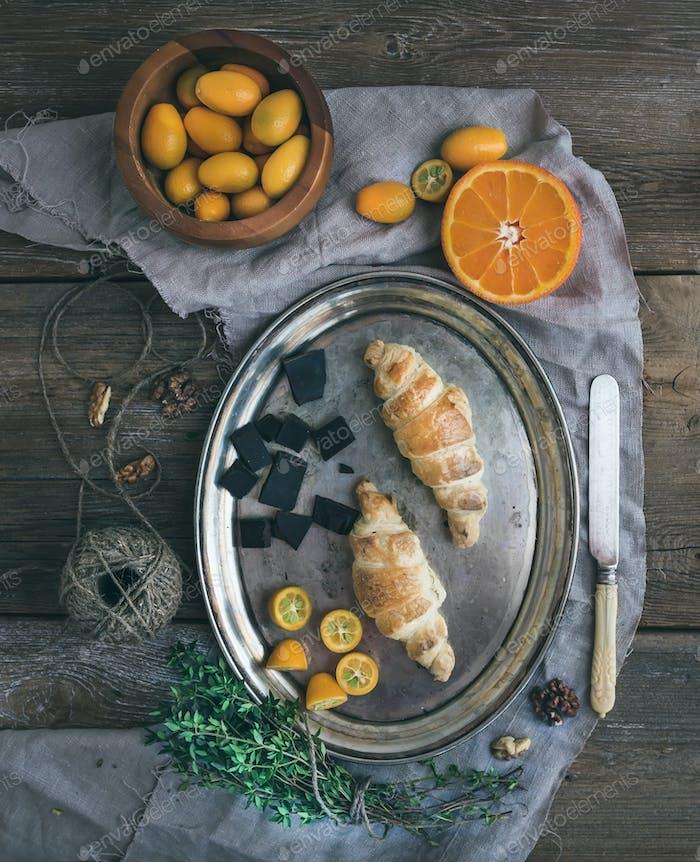 Rustic breakfast set: chocolate croissants on metal dish, fresh