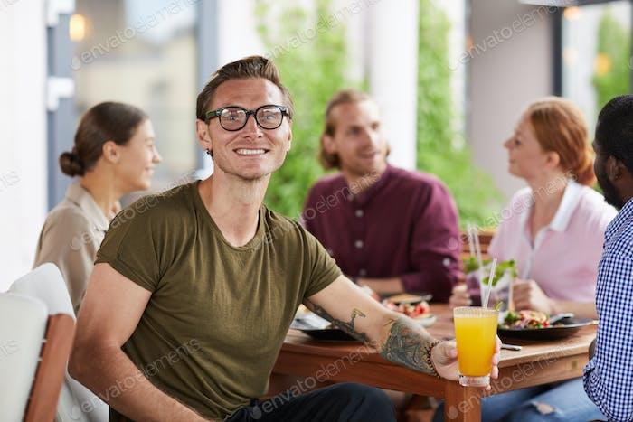 Tätowierter Mann genießen Mittagessen mit Freunden im Café