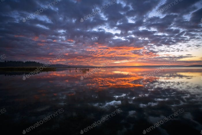 Sunset sky reflected in a lake, and clouds in the sky.