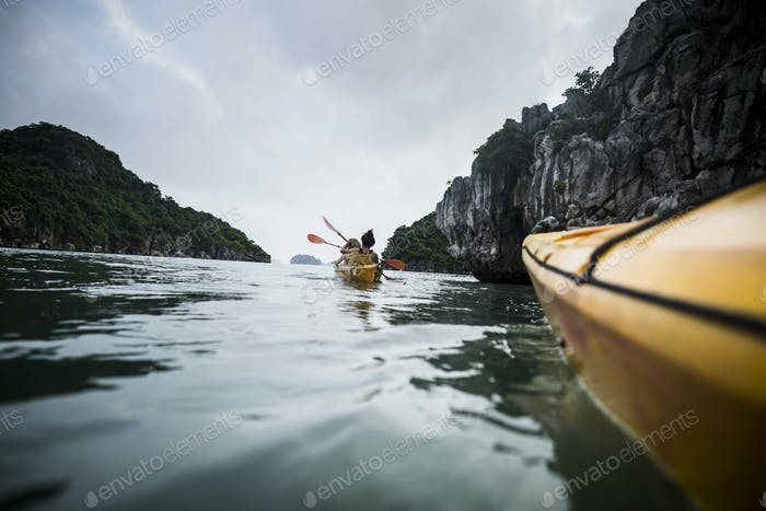 Gruppe von Kajakfahrern rudern in einer Bucht inmitten von Kalkstein-Karstformationen.