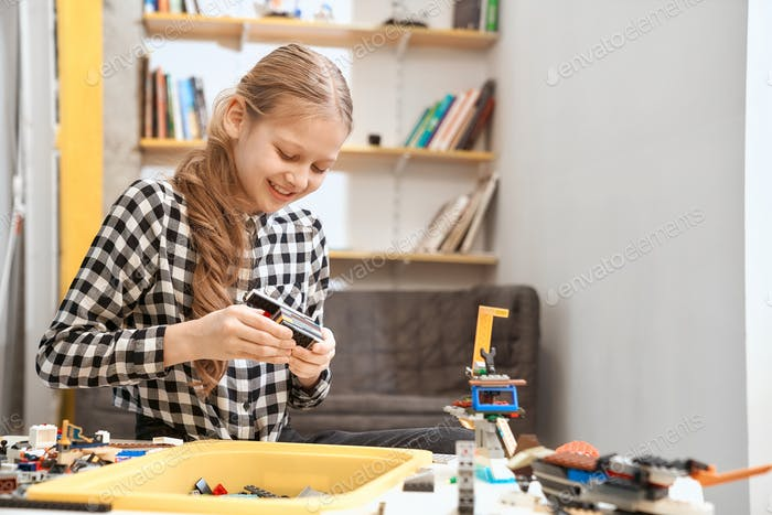 Caucasian girl using building kit