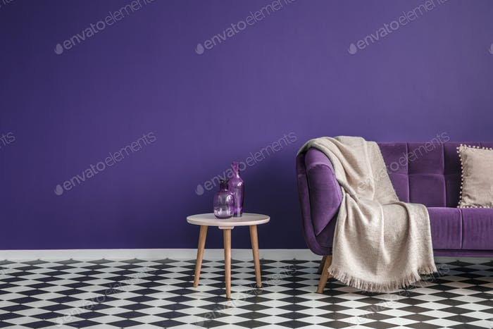 Dark purple sofa with a blanket beside a small table with bottle