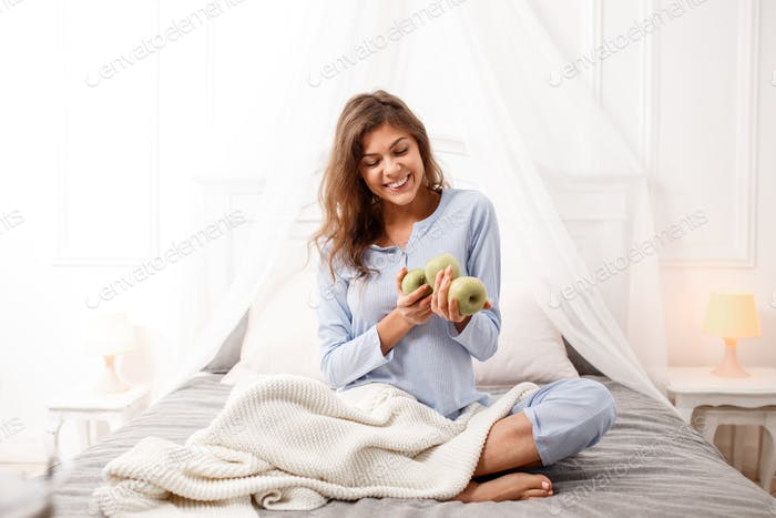 Smiling brunette girl in the light-blue pajama sits on the canopy bed with green apples in her hands