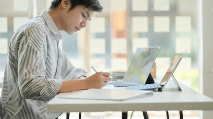 Young professional businessman is thinking of future project with a laptop in comfortable office.