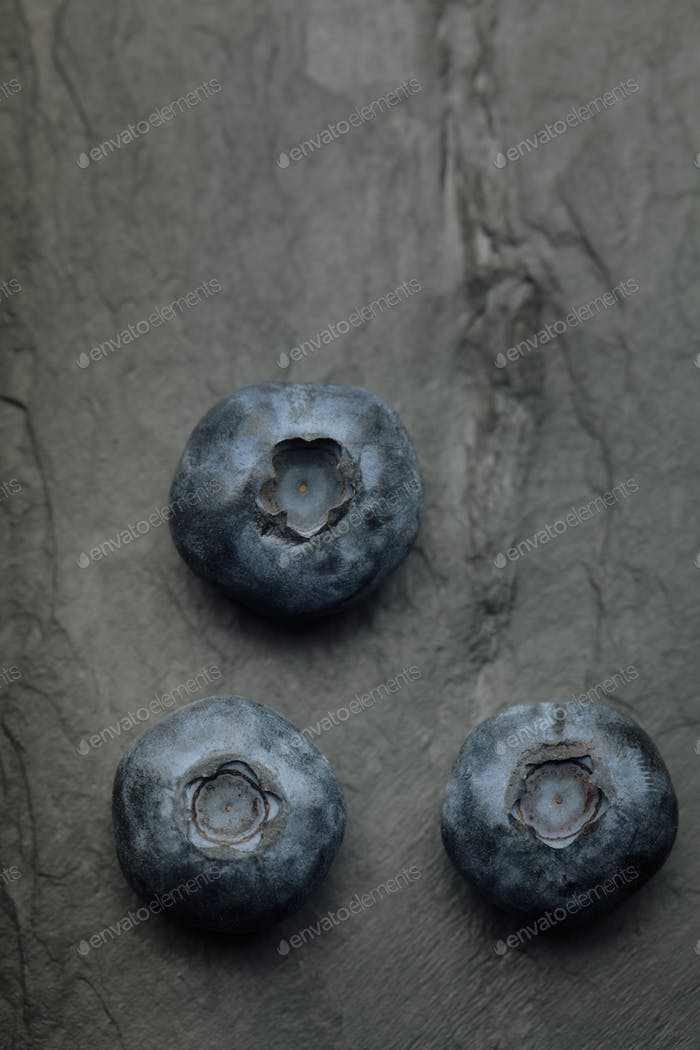 A macro shot of a bunch of blueberries on a dark vintage slate o