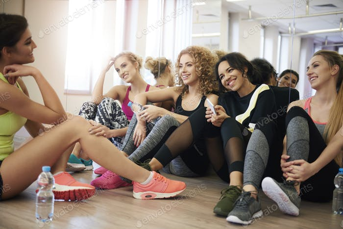 women resting on the floor of gymnasium