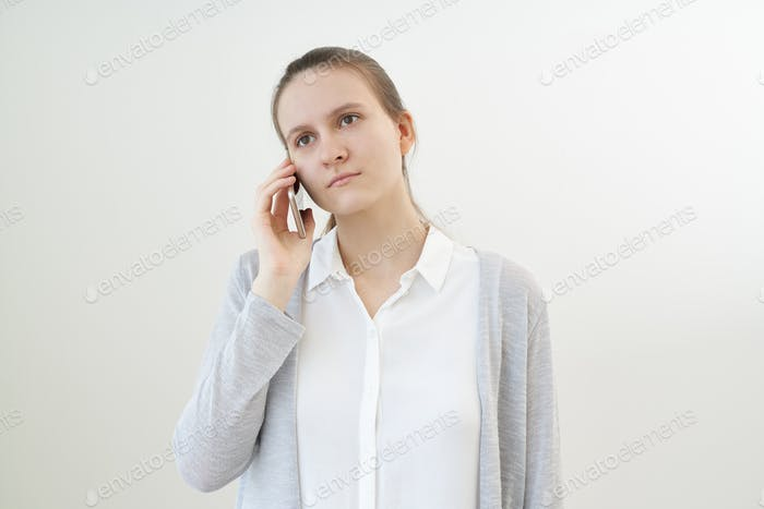 Calm, unemotional woman talks on phone, listens to other person, does not react.