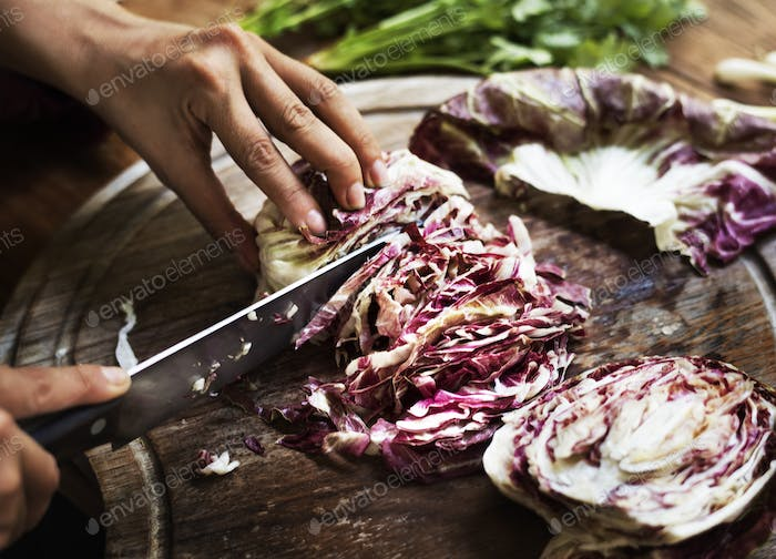 Closeup of hands with knife cutting cabbage on wooden cut board