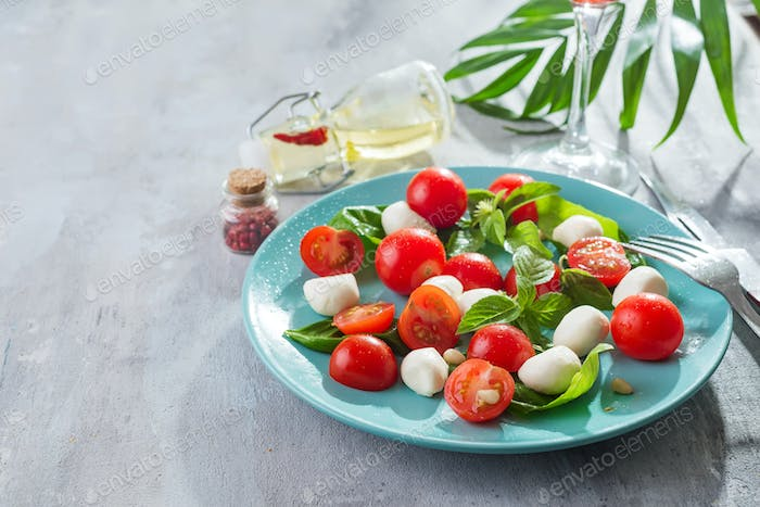 caprese salad with ripe cherry tomatoes and mini mozzarella cheese balls with fresh basil leaves