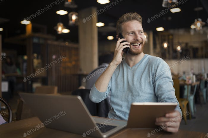 Young happy man having phone call in cafe