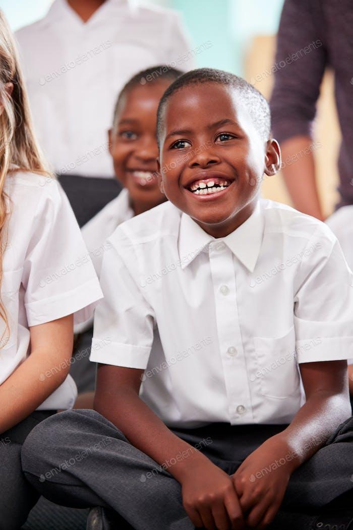 Group Of Elementary School Pupils Wearing Uniform Sitting On Floor Listening To Teacher