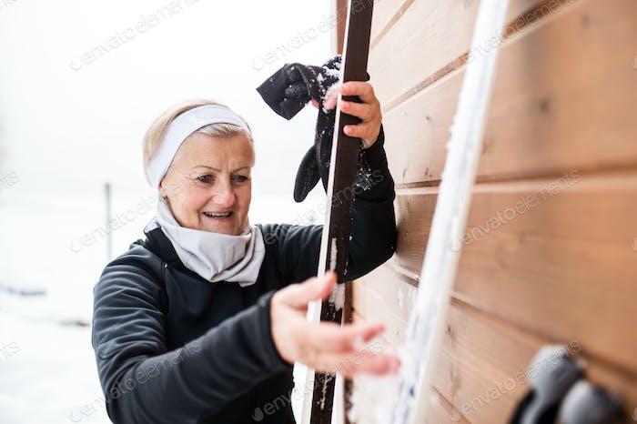 Senior Frau, die sich auf das Skifahren vorbereitet.