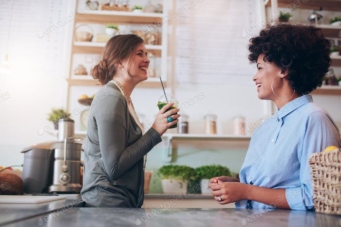 Female employees standing behind juice counter