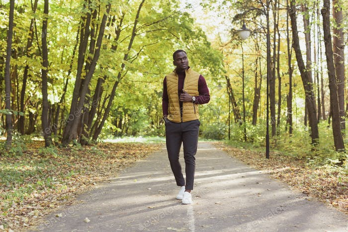 African american student walking in the park in autumn season