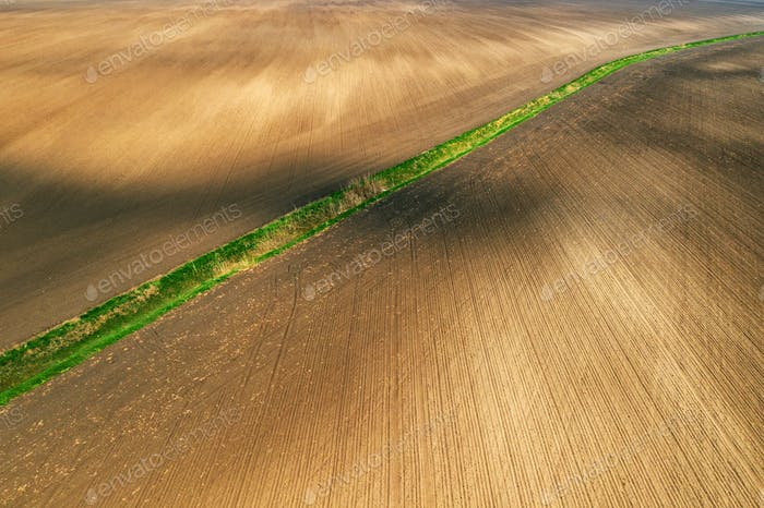 Aerial view of dried irrigation ditch canal through agricultural