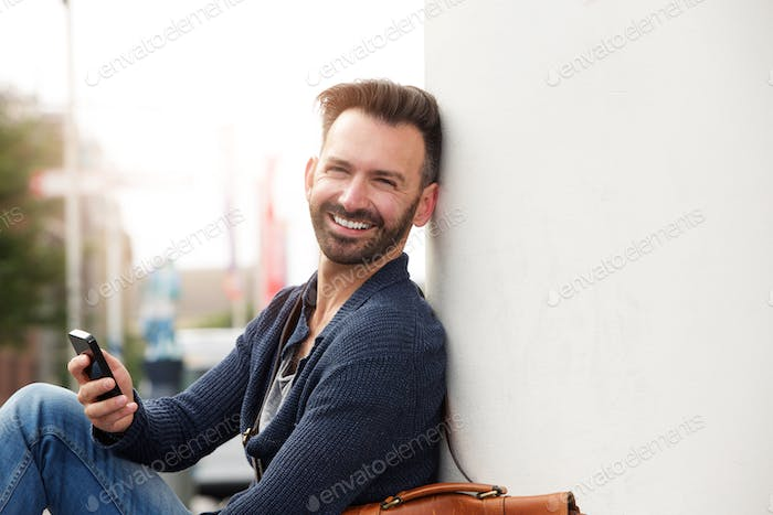 Handsome man with cell phone sitting by a wall outdoors