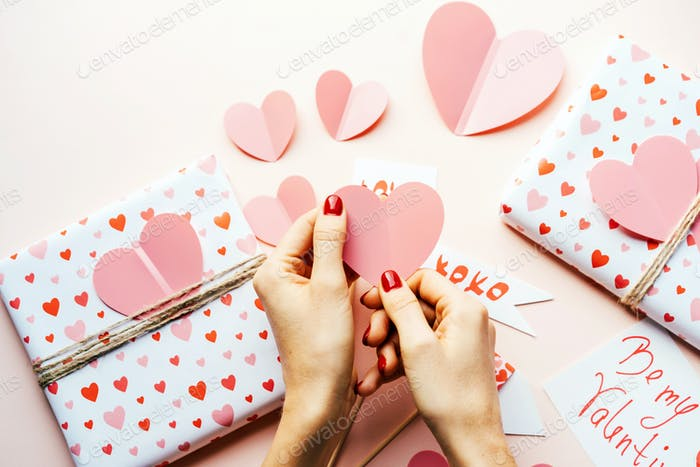 Beautiful hands with manicure decorate the gift box with a big pink heart. Valentine's day content.