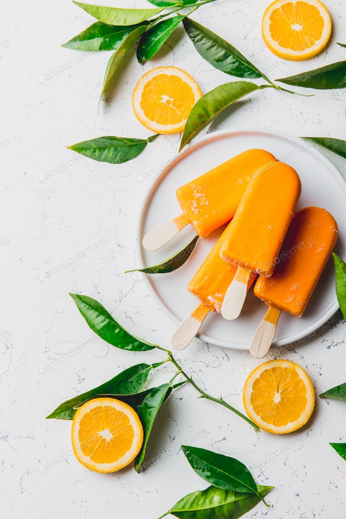 Orange Ice Cream on Stick. White Background with Orange Fruits Slices and Orange Tree Leaves.