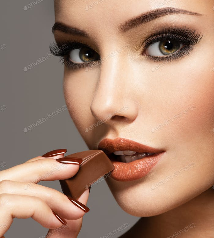 Glamour beautiful woman holds and eats  chocolate candy