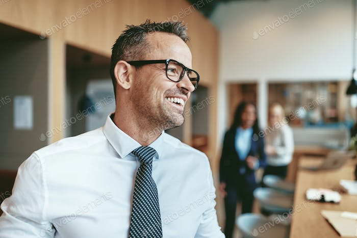 Laughing mature businessman ready for a meeting with office colleagues