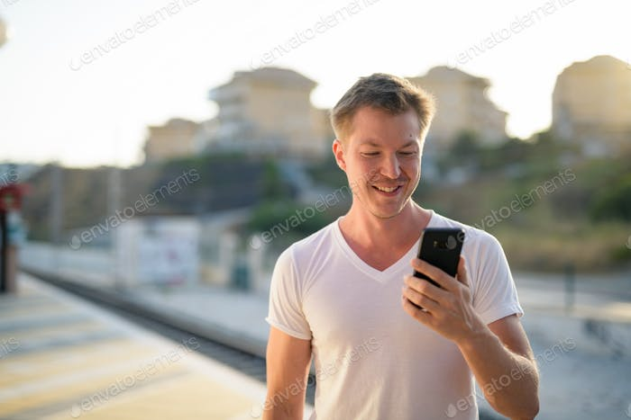 Young Happy Tourist Man Smiling While Using Phone At The Train Station
