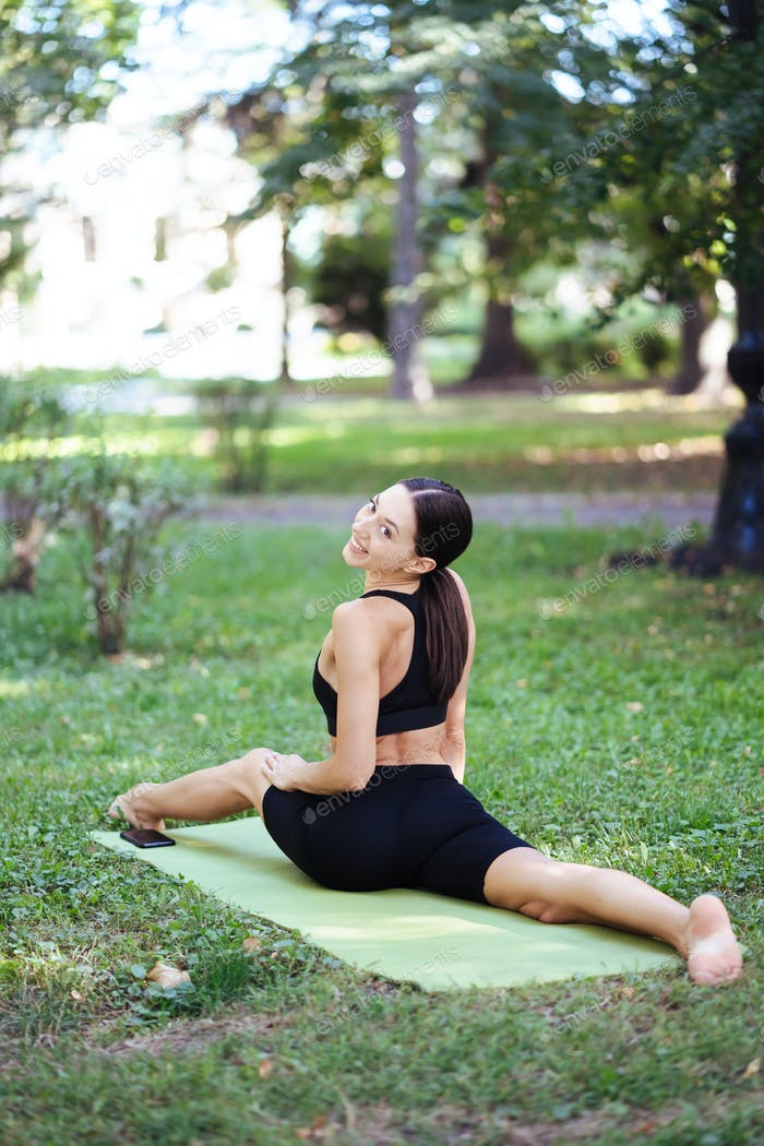 Athletic young woman doing yoga in the Park in the morning