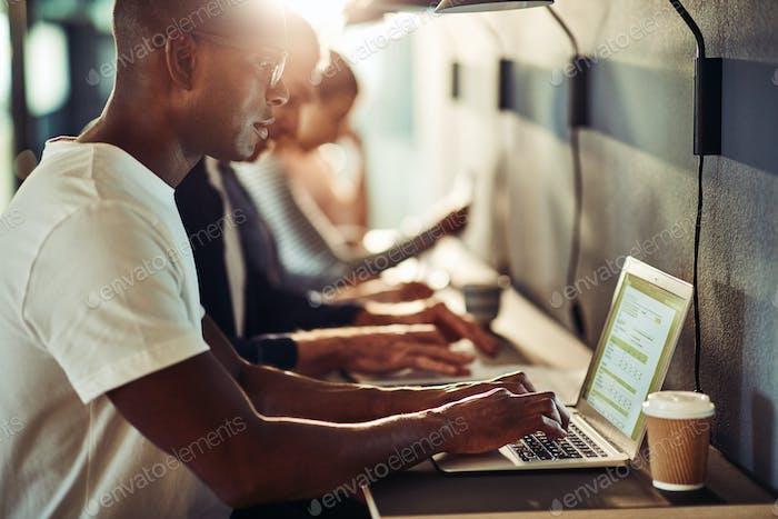 Сосредоточив молодой африканский дизайнер с использованием ноутбука в офисе