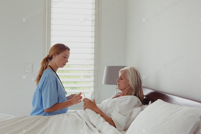 Side view of Caucasian female doctor giving medicine to active senior woman in bedroom at home