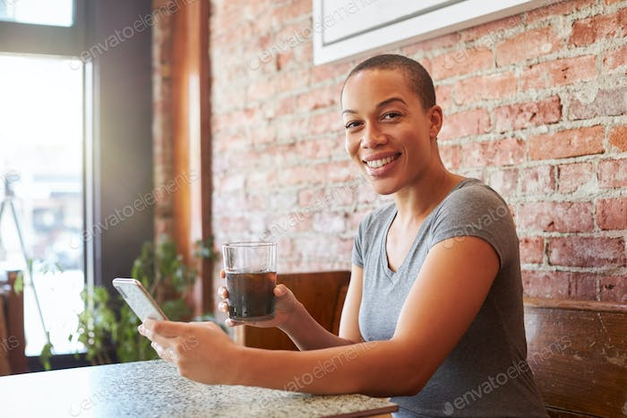 Portrait Of Woman Making Video Call On Mobile Phone Sitting In Coffee Shop