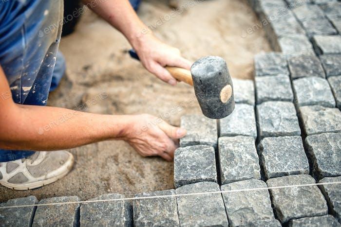 Worker creating pavement using cobblestone blocks and granite stones