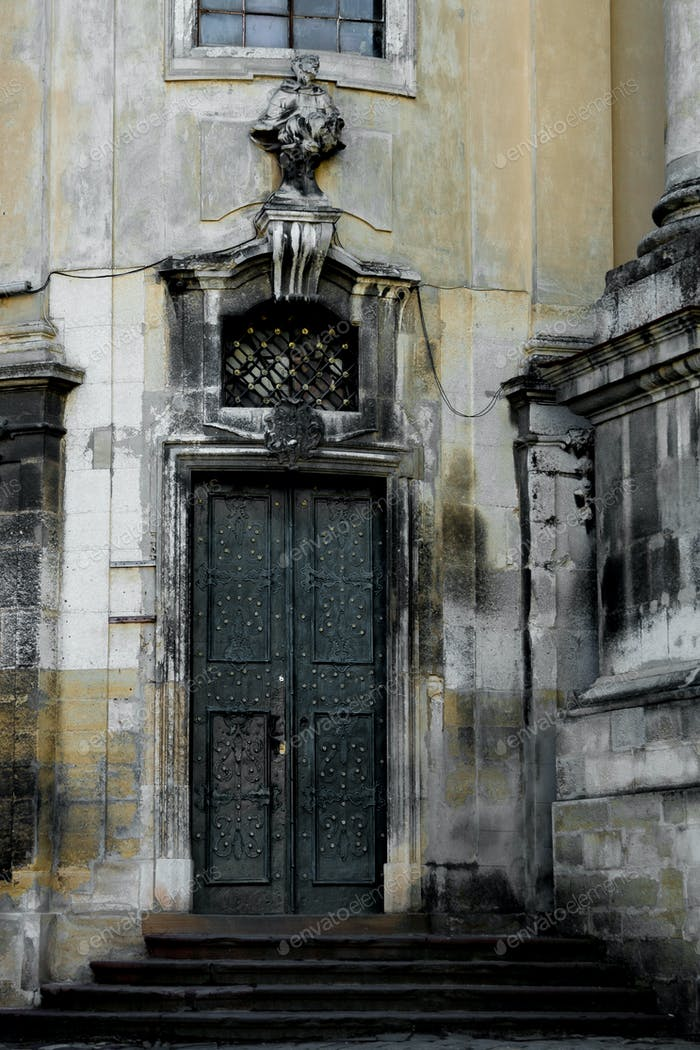 Facade of the Dominican Cathedral, Lviv, Ukraine. Fragment   with door and window  metal grill.