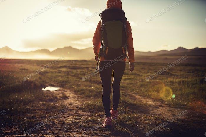Woman hiker hiking on sunset mountains