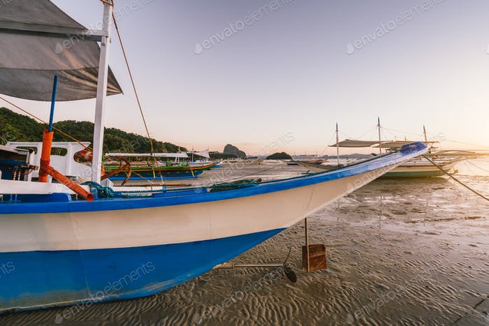 Banca boat on Corong corong beach in sunset light. El Nido, Philippines