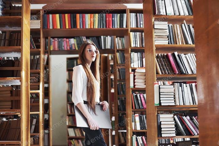 Junge schöne Frau ist eine Studentin in einer Bibliothek mit ihrem Laptop