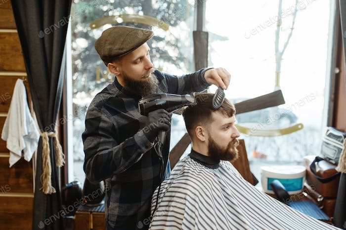 Barber with comb and hairdryer makes a hairstyle