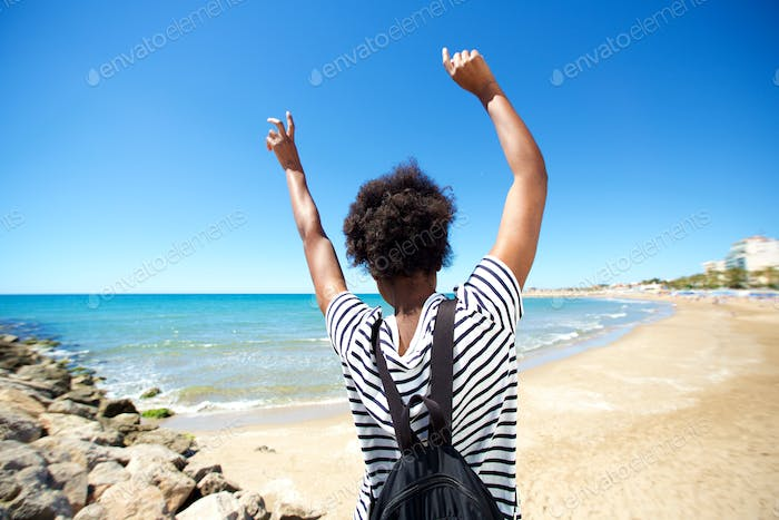 Behind of young black woman enjoying on the beach with her hands raised