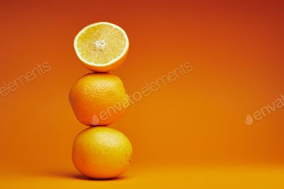 close-up view of whole and sliced oranges on orange background
