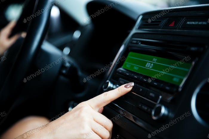 Woman hand pushing the power button in car