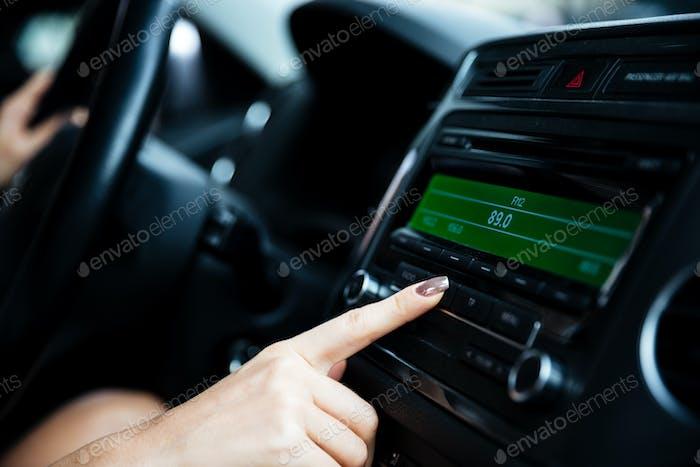 Женщина рука нажатием кнопки питания в автомобиле
