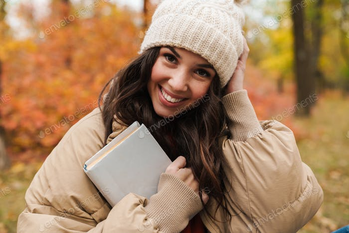 Happy attractive young woman with a book