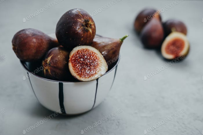 Fresh figs in bawl on gray background