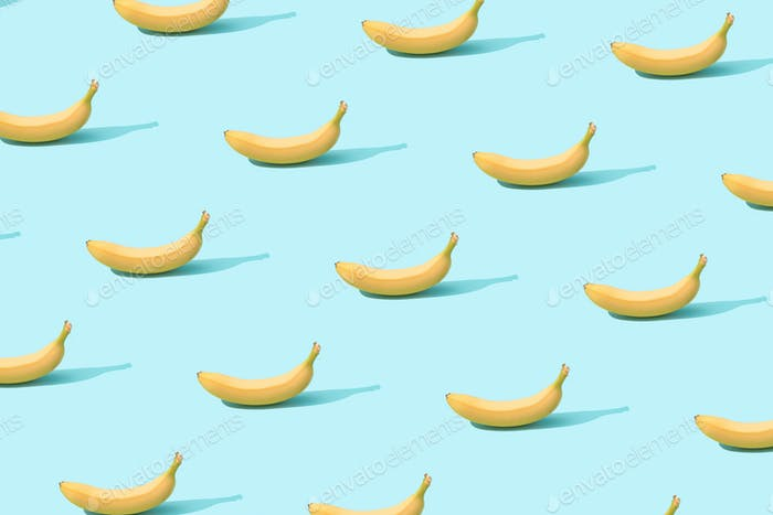 rendy sunlight Summer pattern made with fresh banana fruit on bright light blue background.
