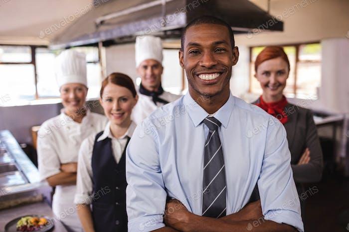 Grupo de personal del hotel de pie con los brazos cruzados en la Cocina del hotel