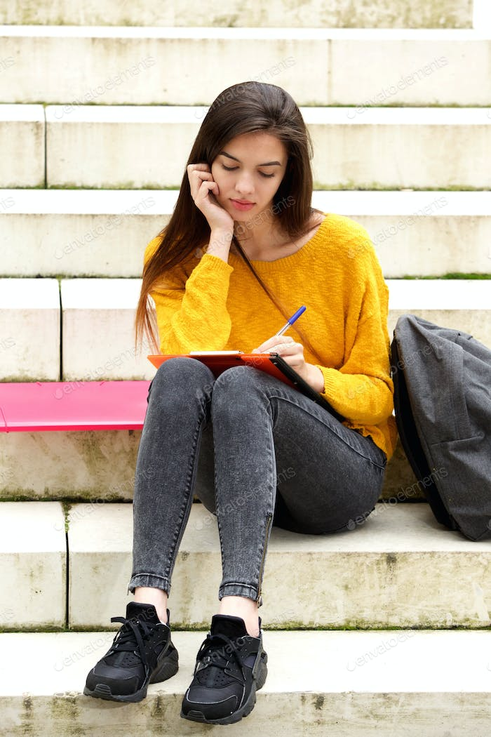 Attractive student sitting on steps thinking