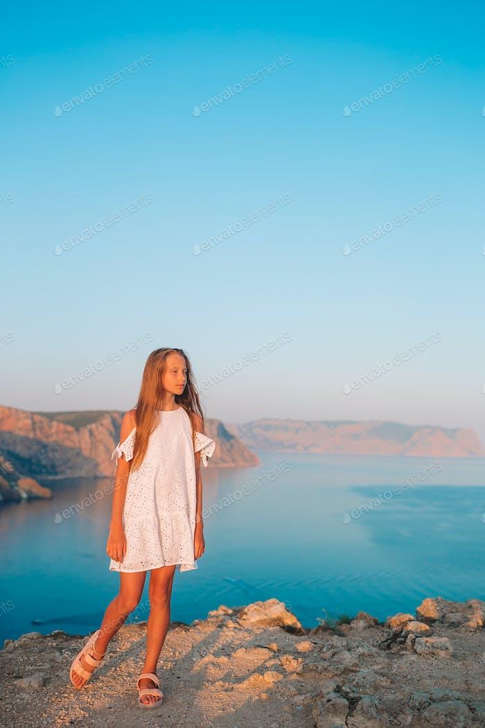 Kleines Mädchen auf einem Berg mit Blick auf das Tal vor Sonnenuntergang
