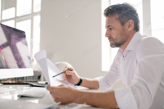 Mature serious engineer in white shirt pointing at sketch while checking it